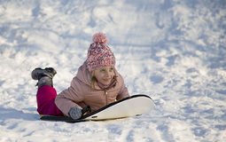 在雪的女孩骑马在冬时滑 免版税库存照片