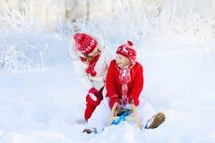 在雪的孩子戏剧 冬天孩子的雪橇乘驾 免版税库存照片