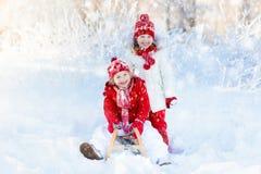 在雪的孩子戏剧 冬天孩子的雪橇乘驾 免版税图库摄影