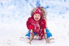 在雪的孩子戏剧 冬天孩子的雪橇乘驾 库存图片