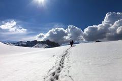 在雪的小径和多雪的高原的两个远足者在太阳春天d 免版税库存照片