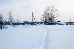 在雪的小径在传统俄国村庄 免版税库存图片