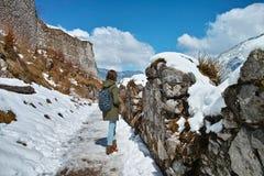 在雪的废墟与妇女远足 免版税库存图片