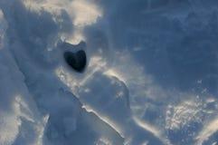在雪的心形的鹿蹄印刷品 免版税库存图片