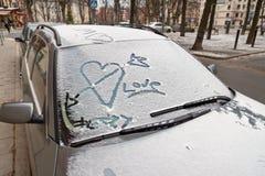 在雪的情人节街道画在汽车挡风玻璃  免版税库存照片
