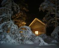 在雪的拉普兰客舱在晚上 图库摄影