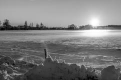 在雪的日落在一个空和冻结的农村领域 免版税库存图片