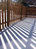 在雪的木篱芭阴影 库存照片
