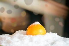 在雪的桔子与圣诞节装饰 免版税库存图片