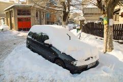 在雪的汽车在街道上在波摩莱,保加利亚,冬天 免版税库存照片
