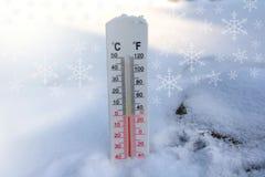 在雪的温度计在摄氏或farenheit显示凝固温度 免版税库存图片