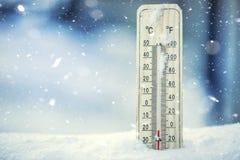 在雪的温度计显示低温在零以下 在摄氏度和华氏低温 免版税库存照片