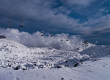 在雪的火山的火山口和滑雪电缆车 库存图片