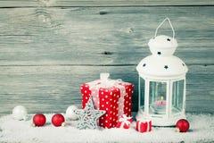 在雪的灼烧的灯笼与圣诞节装饰 免版税库存照片