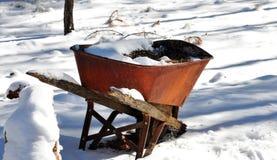 在雪的生锈的独轮车 免版税图库摄影