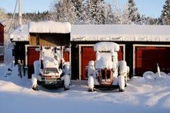 在雪的生锈的老拖拉机 库存图片
