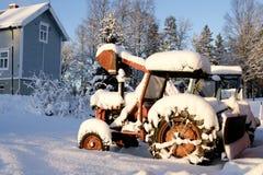 在雪的生锈的老拖拉机 库存照片