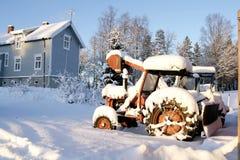 在雪的生锈的老拖拉机 免版税库存图片