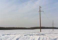 在雪的电帆柱和农业领域 免版税库存照片