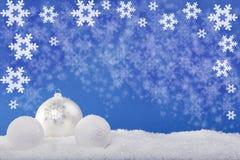 在雪的白色圣诞节球 免版税图库摄影