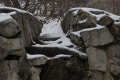 在雪的石头沿有排行河的一个石墙的一条道路 免版税库存照片