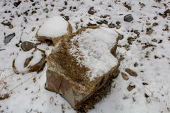在雪的石头沿有排行河的一个石墙的一条道路 图库摄影