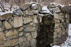 在雪的石头沿有排行河的一个石墙的一条道路 库存图片
