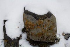 在雪的石头沿有排行河的一个石墙的一条道路 免版税图库摄影