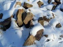 在雪的石头 库存照片