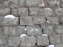 在雪的破碎石块墙壁 水泥在寒冷的冬天 免版税库存照片