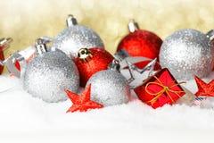 在雪的红色和银色圣诞节球 免版税库存图片