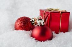 在雪的红色圣诞节装饰 库存照片