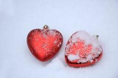 在雪的红色心脏装饰品 库存图片
