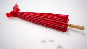 在雪的红色日本伞 免版税图库摄影