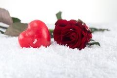在雪的红色玫瑰与心脏蜡烛 免版税库存图片