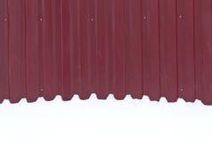在雪的红色金属篱芭 免版税图库摄影