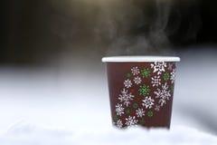 在雪的纸玻璃与热的饮料 免版税库存照片