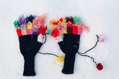 在雪的羊毛被编织的手套 库存照片