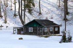 在雪的老木客舱 免版税库存图片