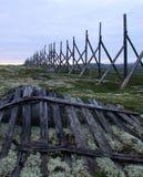 在雪的老木篱芭岗位在小山延迟 免版税库存照片
