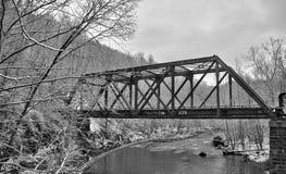 在雪的老火车桥梁 库存照片