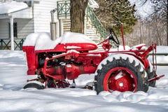 在雪的老红色拖拉机 免版税库存图片