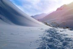 在雪的脚印在冬天山的冬天 免版税图库摄影