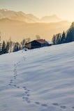 在雪的脚印往在Allgau山的木客舱  免版税图库摄影