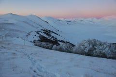 在雪的脚印,在小山的日落在冬天, Sibillini 免版税图库摄影