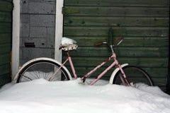 在雪的自行车由老棚子 免版税库存照片