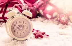 在雪的葡萄酒闹钟在圣诞节礼物背景 免版税图库摄影