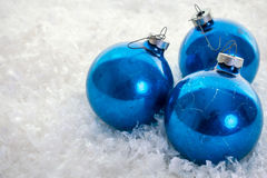 在雪的蓝色圣诞节装饰品 库存照片