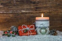 在雪的蜡烛和圣诞节礼物与自然装饰 库存照片