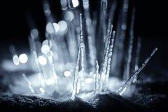 在雪的被阐明的冬天石笋冰柱在黑暗的晚上 免版税库存照片